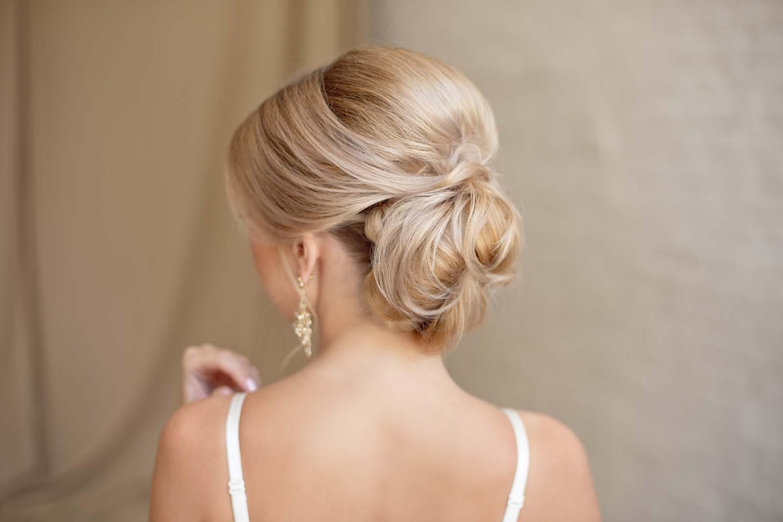 Novia rubia luciendo un peinado de moño bajo sencillo y elegante